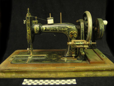 Hand operated, wheel-driven, sewing machine.