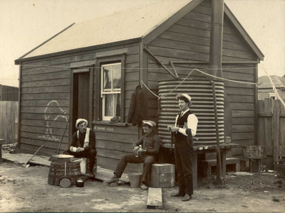 Photo of three miners outside their hut.