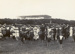 Black and white photograph of a large group of people on a field surrounding the Walsh brothers' plane Manurewa; 1911; 04/077/074