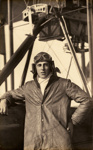 Black and white photograph of F. S. Gordon, graduate of the Walsh Brothers Flying School, wearing pilot's clothing standing by a Walsh Flying boat
