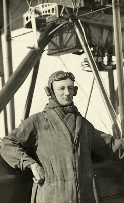 """Black and white portrait of Bob Going wearing a pilot's uniform, standing beside a Walsh Flying boat """"D""""; 1916-1924; 04/071/098"""