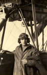 Black and white photograph of C. W. Gillies, graduate of the Walsh Brothers Flying School, wearing pilot's clothing standing by a Walsh flying boat