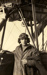 """Black and white photograph of C. W. Gillies, graduate of the Walsh Brothers Flying School, wearing pilot's clothing standing by a Walsh flying boat """"D""""; 1916-1920; 04/071/086"""