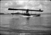 Black and white photograph of a Walsh Brothers seaplane landing on the beach, presumably at Mission Bay; 1915-1927; 04/077/012