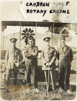 Black and white photograph of four men in uniform standing in front of a Caudron  aeroplane; 1916-1920; 04/071/094