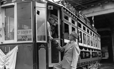 Charles Bowden is stepping up the stairs and shaking hands with one of the two uniformed men standing inside the tram no. 11; W.W. Stewart (b.1898, d.1976); 06-836