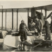 Black and white photograph of parcels being loaded onto a Supermarine Channel flying boat  of the Walsh Brothers Flying School for delivery of the NZ Herald containing election results of 1922; 1...