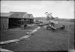"""Black and white photograph of Walsh Brothers Flying School planes outside their hangars at Mission Bay. Curtiss """"C """" in right foreground; 1915-1927; 04/077/018"""