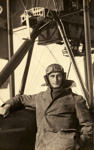Black and white photograph of G. C. Hyde, graduate of the Walsh Brothers Flying School, wearing pilot's clothing standing by a Walsh Flying Boat