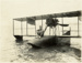 Black and white photograph of a man sitting cross-legged on the nose of a Curtiss flying boat; 1916-1924; 04/071/101