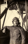 Black and white photograph of Eric Strain, graduate of the Walsh Brothers Flying School, wearing pilot's clothing standing by a