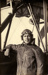 """Black and white photograph of Eric Strain, graduate of the Walsh Brothers Flying School, wearing pilot's clothing standing by a """" Roberts """" flying boat; 1916-1920; 04/071/077"""