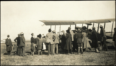 Black and white photograph of aeroplane on the ground  at Tomoana Hastings surrounded by people; 1915-1920; 04/071/097