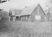 Photograph of Mission house with New Zealand Flying School hangar in background; Unidentified; Circa 1920; 06/097/035