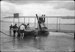"""Black and white photograph of a Walsh Brothers Curtiss """"C"""" flying boat in the water, with five men holding it; 1915-1927; 04/077/013"""