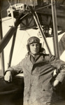 Black and white photograph of C. P. Todd, graduate of the Walsh Brothers Flying School, wearing pilot's clothing standing by a Walsh Flying Boat