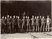 Black and white photograph of 15 Walsh Brothers Flying School pilots in NZFS uniform standing in front of a plane in a hangar; 1915-1927; 04/077/025