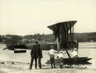"""Black and white photograph of Walsh Brothers Flying School Boeing seaplane """"G"""" at Pahi on the Kaipara Harbour, with children and two men (one being George Bolt) beside it; 1921; 04/077/064"""