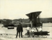 "Black and white photograph of Walsh Brothers Flying School Boeing seaplane ""G"" at Pahi on the Kaipara Harbour, with children and two men (one being George Bolt) beside it; 1921; 04/077/064"