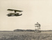 Black and white photograph of the Walsh brothers' first seaplane, flying past Bean Rock lighthouse, 1915, with Vivian Walsh at the controls; 1915; 04/077/069