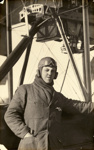 Black and white photograph of J. Woods, graduate of the Walsh Brothers Flying School, wearing pilot's clothing standing by a plane; 1916-1920; 04/071/070