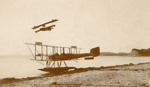 """Black and white photograph of Walsh Brothers Flying School  """"Boeing  1"""" on the beach at Mission Bay, with   Curtiss flying boat """"C"""" overhead; 1915-1927; 04/077/006"""