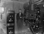 Cinema projector and projectionist in projection room; J G McGuire; 1930s; 13-2151