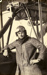 """Black and white photograph of R. M. de Lisle, graduate of the Walsh Brothers Flying School, wearing pilot's clothing standing by a Walsh Flying Boat """"D""""; 1916-1920; 04/071/073"""