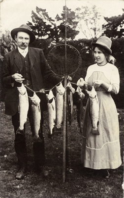 Photograph of a man and woman with seven trout and net; Unidentified; 13-1096