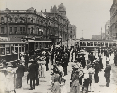 [Crowd of Ellerslie racegoers waiting to board trams at the intersection of Queen and Custom Streets]; Unknown Photographer; [1902-1920]; PHO-2017-5.5