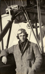 Black and white photograph of A. H. Murison, graduate of the Walsh Brothers Flying School, wearing pilot's clothing standing by a Walsh Flying Boat