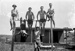 Black and white negative of students of the Walsh Brothers Flying School exercising on a bar; 1915-1927; 04/077/024