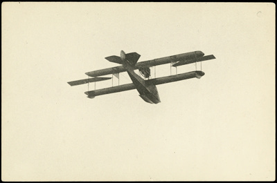 """Black and white photograph of Curtiss """"C"""" flying boat of the Walsh Brothers Flying School in flight, taken from below; 1916-1920; 04/071/093"""