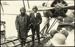 Black and white postcard showing two pilots standing beside a newly landed seaplane, with people looking on; 1916-1924; 04/071/099