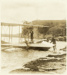 Black and white postcard showing four men alongside a Walsh Brothers Flying School seaplane on the beach; 1915-1924; 04/071/103