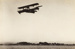 Photograph of a Curtis flying boat bi-plane in air flying looking towards Auckland; Unidentified; Circa 1918; 06/097/028