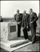 Black and white photograph of George Bolt, Geoff Roberts  ? , (Mr McAlpine, Minister of Civil Aviation), looking at a plaque at Mission Bay to commemmorate TEAL's 21st birthday and the Walsh Brot...