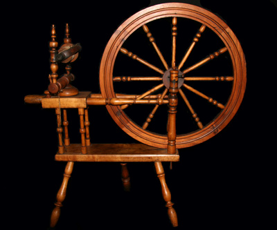 Wooden, three-legged spinning wheel. The wheel has...