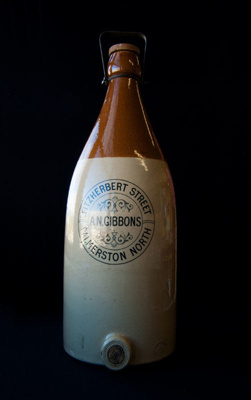 Large stoneware ginger beer bottle. It has a brown...
