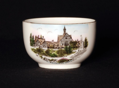 This white souvenir ware porcelain sugar bowl feat...