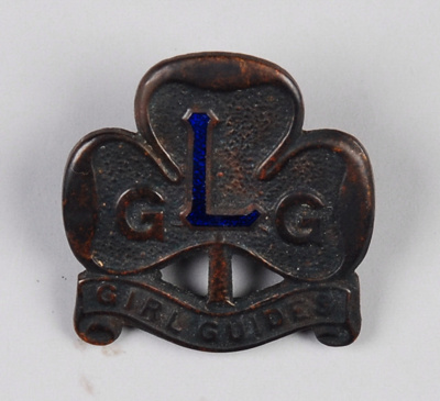 A brass Girl Guide badge with the letter, L, in bl...