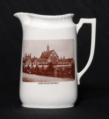 White china jug with pouring lip and handle on its...