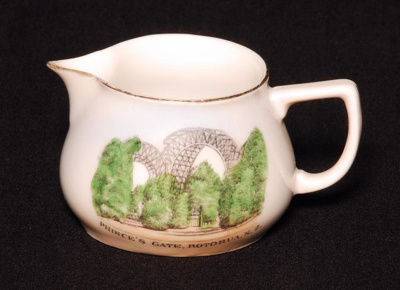 A small white china souvenir milk jug with a colou...