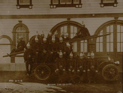 View of firemen posing on a fire engine in front o...