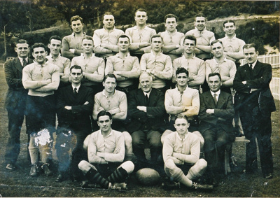 Rugby team photograph in four rows, on a field.