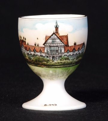 This souvenir ware china egg cup features an image...