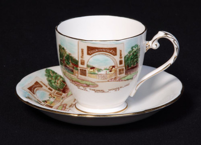 A set of white china souvenir cup and saucer with ...