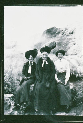 View of three women posing for the camera in front...