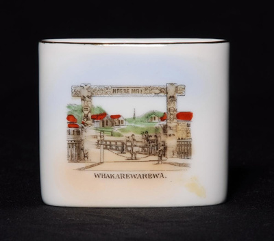 This souvenir ware white china vase, features an i...