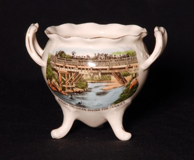 The cauldron is a shaped white ceramic souvenir wa...